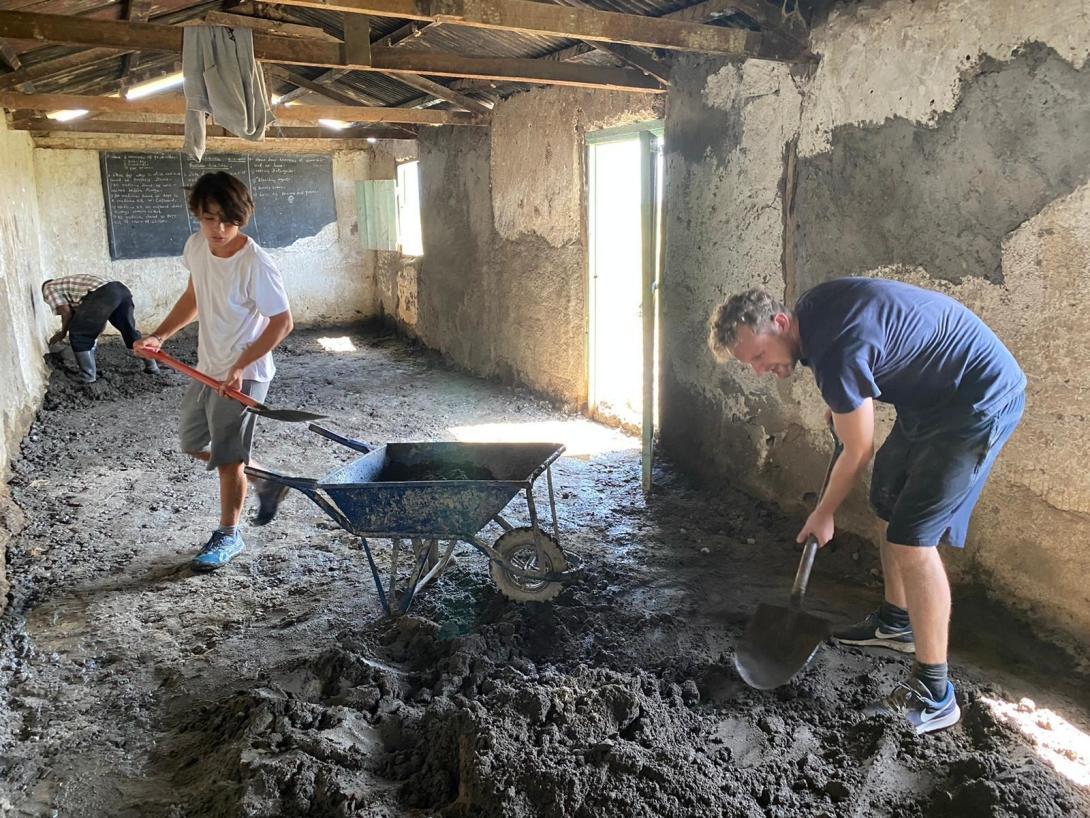 En pappa och en son volontärarbetar med att renovera en skola under deras volontärresa utomlands.